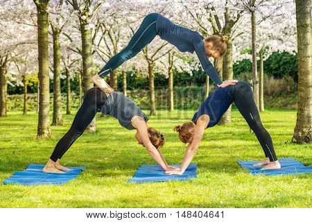 Three young women in downward facing dog pose creating a pyramid