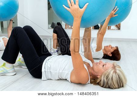 Group of Middle aged women exercising with fitness balls in health center