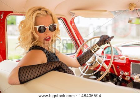 Sexy woman with sun-glasses driving a retro car