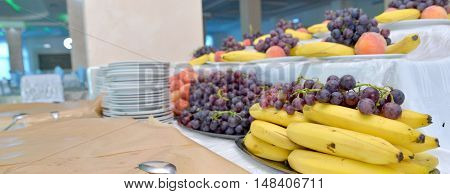 picture of a grapes bananas oranges on a table