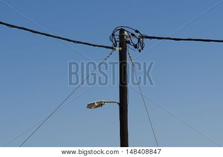 Power line on wooden poles with street light on the background blue sky