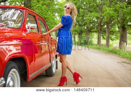 Sexy woman opening red retro cars door