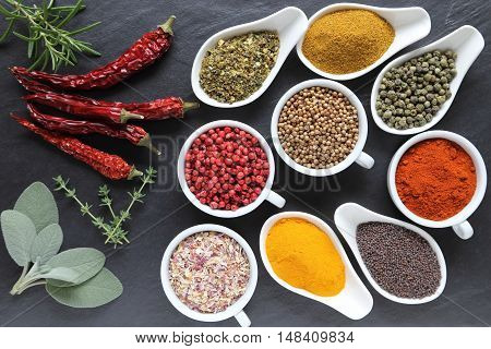 Aromatic and colorful spices in ceramic containers on a dark background.