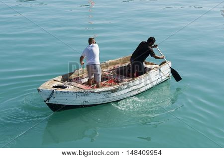 Zakynthos Greece July 15 2016: Two men row in the opposite direction on an old wooden boat damaged