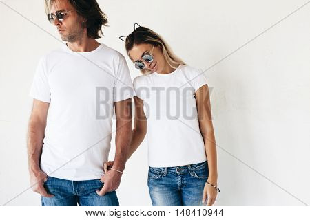 Two hipster models man and woman wearing blanc t-shirt, jeans and sunglasses posing against white wall, toned photo, front tshirt mockup for couple