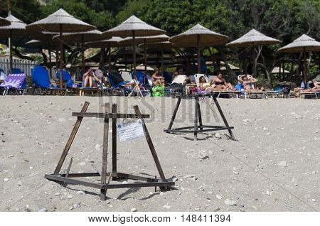 Zakynthos Greece July 16 2016: Island of Zakynthos Greece National Marine Park Dafni beach Caretta turtle nest protection on the bottom tourists in the seaside complex