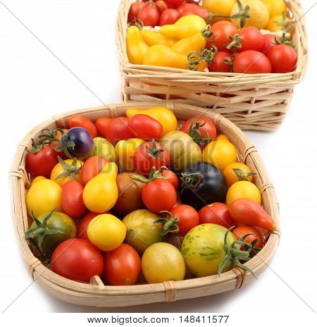 Colorful different kind tomatoes in wooden basket.