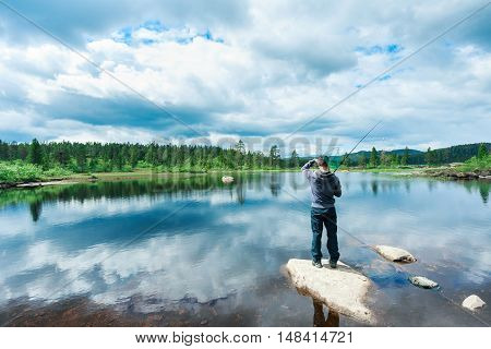 A young man fly-fishing in Kongberg Norway