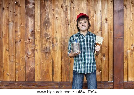 Boy painting wooden wall - large copy space