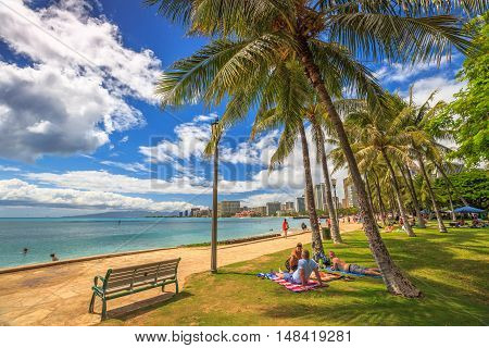 Waikiki , Oahu, HI - August 27, 2016: people take the sun lying on the lawn fronting the popular Queen's Beach section of Waikiki Beach. Wooden benches on Queens Beach boardwalk.