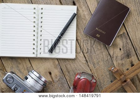 Vintage retro travel background. Retro camera balsa wood model airplane empty notebook and passport on wooden table background.