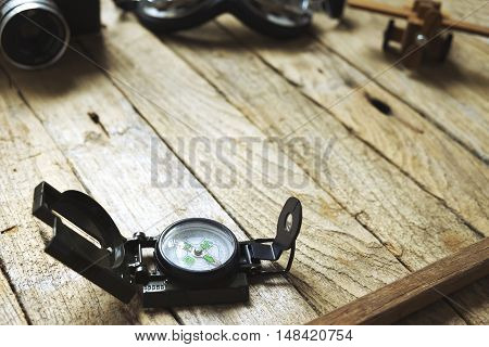 Compass on wooden background. Blur vintage camera glasses and balsa wood model airplane. Vintage filter travel concept.