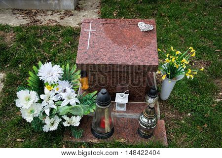 Urn grave with cross on traditional cemetery. Votive candles lantern and flowers on tomb stones in graveyard. All Saints' Day. All Souls' Day. Gravestones in village Tvrdomestice, Slovakia poster