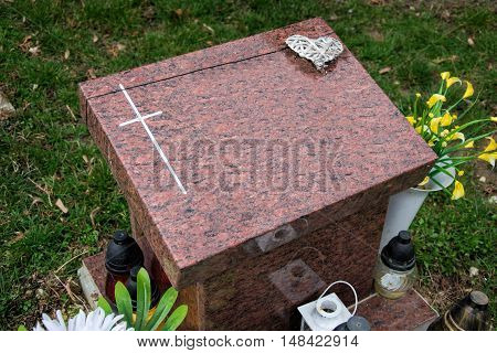 Urn grave with cross on traditional cemetery. Votive candles lantern and flowers on tomb stones in graveyard. All Saints' Day. All Souls' Day. Gravestones in village Tvrdomestice, Slovakia