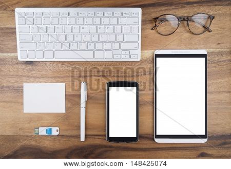 Still life of view from above of office supplies white paper note white pen blank mobilephone sceen empty tablet scree keybord usb drive and vintage glasses on wooden working table background.
