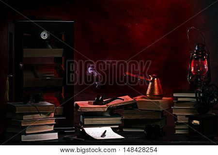 Vintage private office desk with stacks of books, humidor and smoking pipe in the light of kerosene lantern