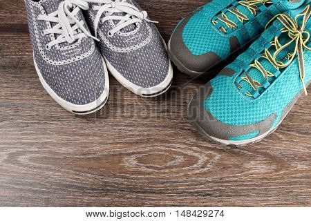 Two pairs of colorful sneakers laid on the wooden floor background