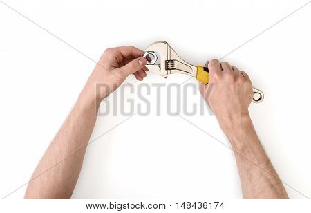 Close up view of a man's hands working with adjustable wrench, isolated on white background. Mechanic and repairman. Handyman. DIY concept. Tools and instruments.