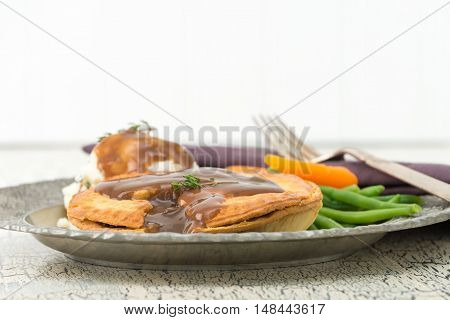 Beef and mushroom meat pie served with mashed potatoes and fresh vegetables.