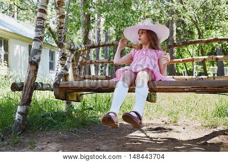 Little girl in pink dress and sunhat sits on wooden swings under trees.