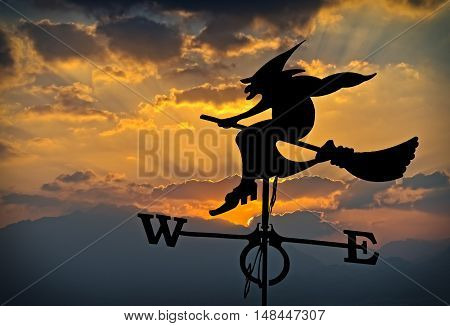Silhouette of weather vane with witch flying on broomstick