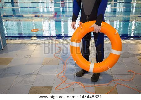 Instructor is holding lifebuoy near pool in training center.