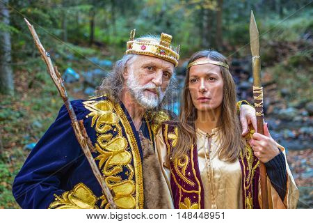 Portrait of king and queen warriors outdoors in the middle of colorful autumn forest