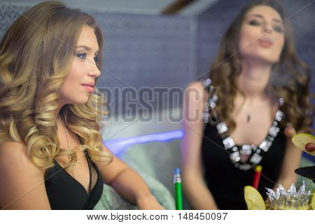 Cute young woman have a rest in smoky room, focus on the left woman.