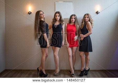 Four cute young women with beautiful legs in short dresses