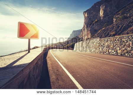 Asphalt Road And Road Sign In Mountains At Sunrise
