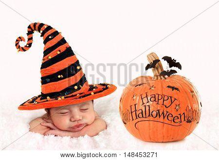 Newborn baby girl wearing a Halloween witch hat, next to a pumpkin