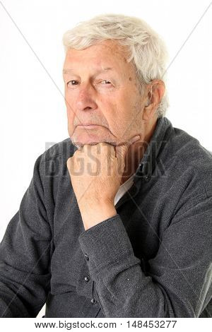 Senior gentleman wearing a hearing aid and  looking sad with visible tears running down his cheek.