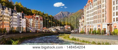 SOCHI RUSSIA - OCTOBER 31 2015: Rosa Khutor hotel buildings and infrastructure of Alpine ski resort. Constructed from 2003 to 2011. Krasnaya Polyana Sochi Krasnodarskiy kray Russia. Multi-storey modern building on banks of Mzymta river