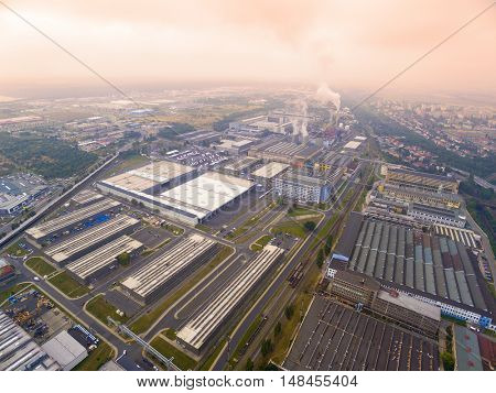 Toxic smog over industrial zone. Aerial view to machinery and steelworks in Pilsen suburb. Heavy industry from above. Czech Republic, European Union.
