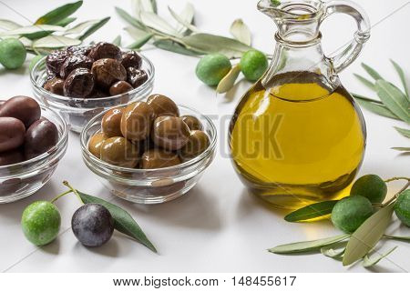 Glass bottle with premium virgin olive oil near variety of olives in bowls, olive tree branches with olives on the white background. Premium virgin olive in bottle and variety of olives. Horizontal.