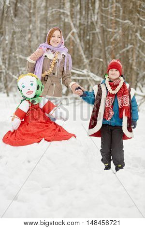 Teenage girl with shawl on head and boy stand holding hands near stuffed dummy Maslenitsa, sitting on snowbank in winter park.