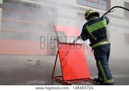 Firefighter with hose directs water on red shield. Inscription on the uniform Fire protection MES of Russia.