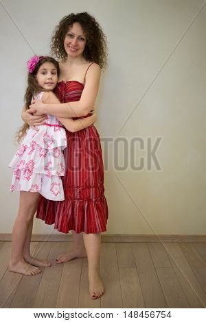 Mother and her daughter are standing barefoot on the floor and hugging.