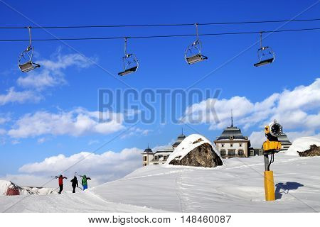 Chair-lift In Blue Sky And Three Skiers On Ski Slope At Sun Nice Day