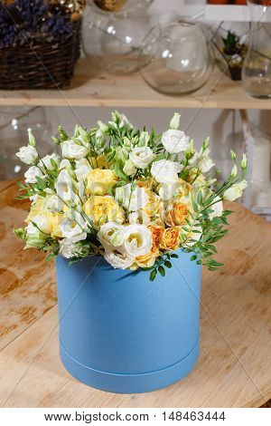 Rich bunch eustoma white and yellow roses of composition in hatbox. A fresh bouquet flowers different colors mix.
