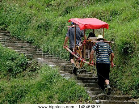 Longsheng China - May 2 2006: Porters transport tourists up stone mountainside stairs to Ping-An Village using covered wooden sedan chairs
