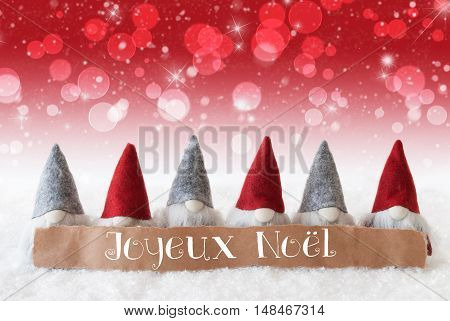 Label With French Text Joyeux Noel Means Merry Christmas. Christmas Greeting Card With Red Gnomes. Sparkling Bokeh And Christmassy Background With Snow And Stars.
