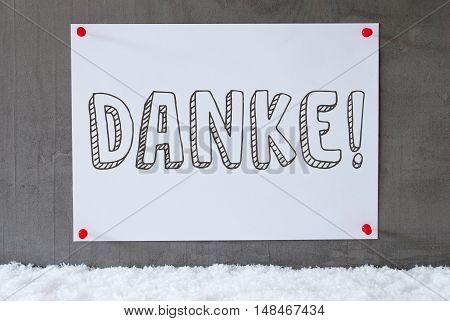 Label With German Text Danke Means Thank You. Urban And Modern Cement Wall As Background On Snow