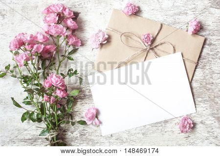 blank white greeting card with pink rose flowers bouquet and envelope with flower buds on white wooden background. vintage toning