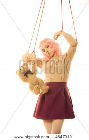 Mental disorder concept. Young woman girl stylized like marionette puppet on string with teddy bear toy on white background