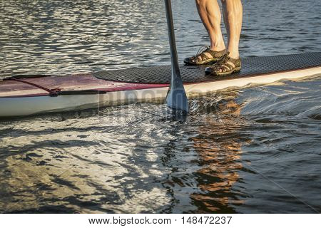 stand up paddling abstract - male feet on a paddleboard
