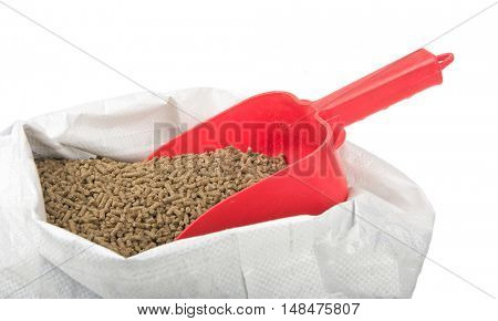 Red feed scoop inserted in a bagful of pelleted horse feed, isolated on white