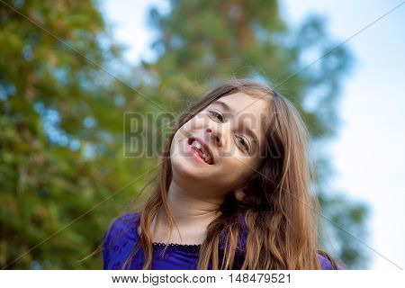 A girl smiling with a missing front tooth. Her head is tilted to the side and there is lots of copy space in the tree behind her.