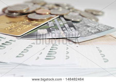Concept of spending : Close up of credit cards and coins on Thai Baht money