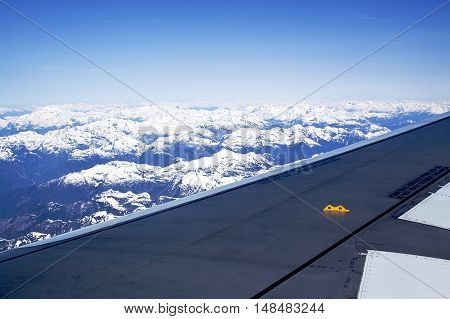 Airplane wing cutting from left to right as seen from the airplane and a beautiful vista of the Rocky Mountains below. On a sunny day, with blue skyline and cobalt sky in the distance.